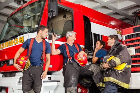 leaning on the truck: Team of happy firefighters conversing while leaning on trucks at fire station Stock Photo