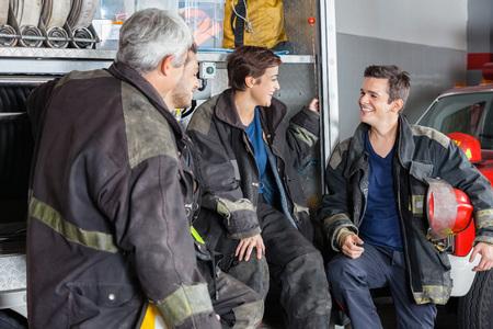 bombero: Bomberos Hombres y mujeres que conversan por cami�n en la estaci�n de bomberos
