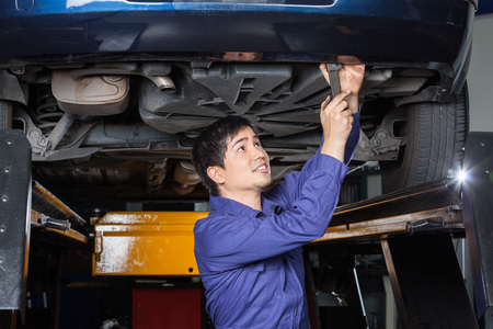 underneath: Male mechanic using wrench underneath lifted car at auto repair shop Stock Photo