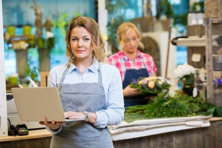 Ritratto di fiorista femminile utilizzando il computer portatile con il collega che lavora in fondo al negozio di fiori