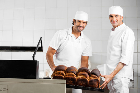 food industry: Portrait of confident male Bakers packing bread loaves in bakery