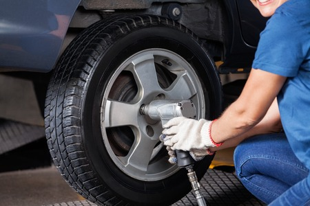 impact wrench: Midsection of female mechanic using pneumatic wrench to fix car tire at repair shop Stock Photo