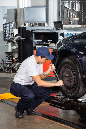 crouching: Male mechanic crouching while fixing car tire at repair shop Stock Photo