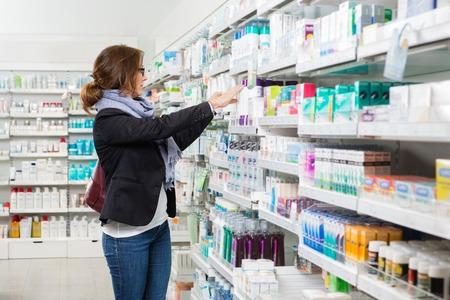 farmacia: Cliente mujeres Mediados de adultos de elegir un producto en la farmacia