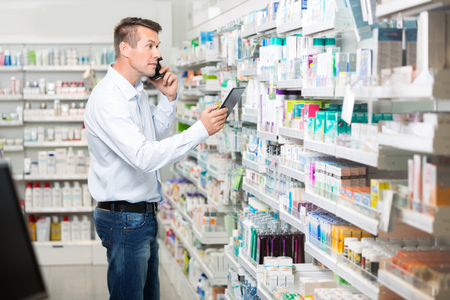 mid adult male: Mid adult male customer using mobile phone and digital tablet while looking at products in pharmacy