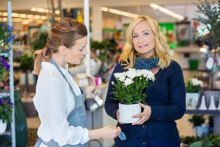 salesgirl: Portrait of female customer being assisted by salesgirl in buying flower plants at store