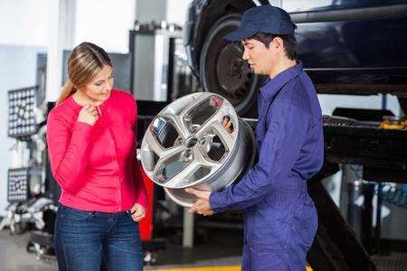 hubcap: Male technician showing metallic hubcap to female customer at garage