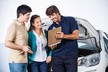 Šťastný muž mechanik vysvětlovat dokumenty pár v opravně auto Reklamní fotografie