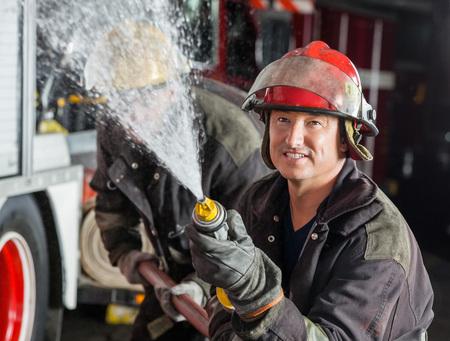 bombera: Bombero de sexo masculino confidente pulverización de agua mientras practicaba con su colega en la estación de bomberos Foto de archivo