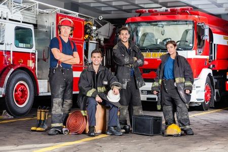 FIRE ENGINE: Portrait de pompiers de confiance avec l'équipement contre des camions à la caserne de pompiers