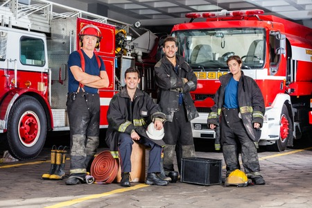fire protection: Portrait of confident firefighters with equipment against trucks at fire station Stock Photo