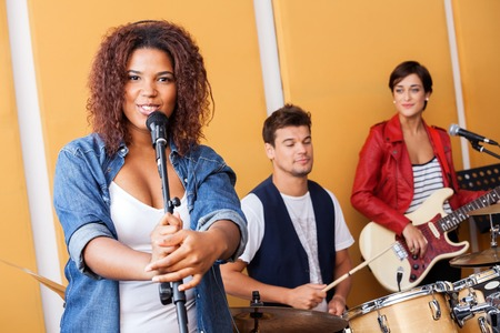 musical band: Portrait of female singer performing with band members in recording studio