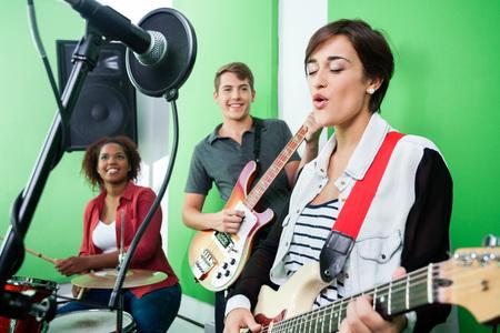 cantando: Mujer joven que canta mientras que la banda que toca el instrumento musical en el estudio de grabación