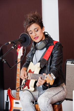 spiked hair: Funky woman playing guitar in recording studio