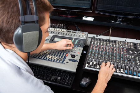 mixing: High angle view of young man mixing audio in recording studio Stock Photo
