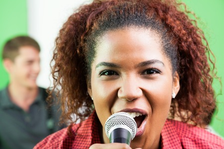 excited woman: Closeup portrait of excited woman singing in recording studio