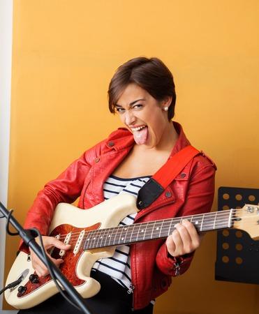 sacar la lengua: Portrait of joyful guitarist sticking out tongue while performing in recording studio