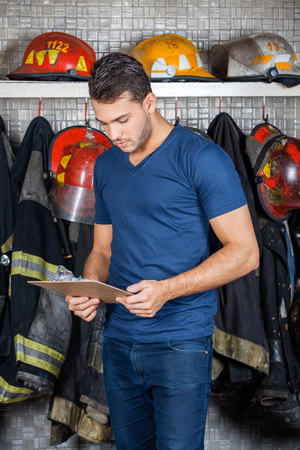 fire fighting equipment: Firefighter reading clipboard against uniforms hanging at fire station