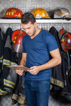 firefighter: Portapapeles lectura bombero contra uniformes colgando en la estaci�n de bomberos