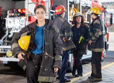 bombero: Retrato de firewoman conf�a en la celebraci�n casco mientras colegas masculinos discutir por cami�n al fondo ya la estaci�n de bomberos