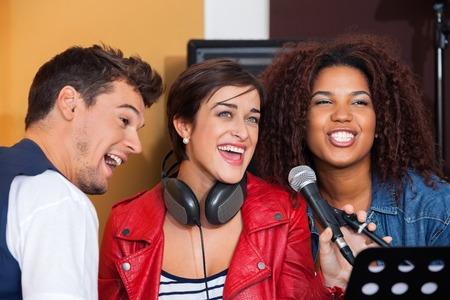 armonia: Feliz macho y miembros de la banda femenina cantando en el estudio de grabación