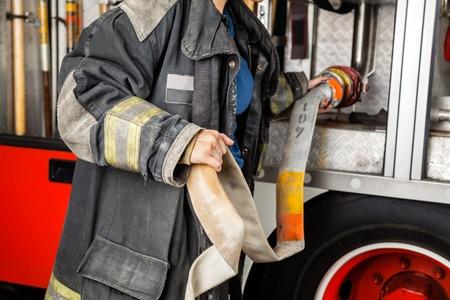 à  à     à  à    à  à female: Sección media de firewoman ajustar la manguera de agua en camión en la estación de bomberos