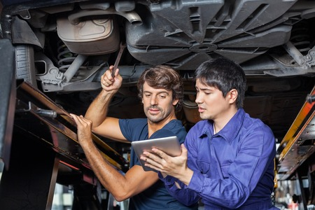 car mechanic: Male mechanics using digital tablet while working under lifted car at auto repair shop