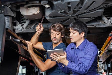 mecanico: Mec�nicos de sexo masculino que usa la tableta digital mientras trabaja bajo el coche levantado en la tienda de reparaci�n de autom�viles