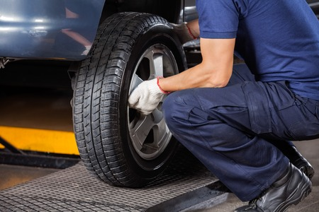 Low section of mechanic fixing car tire at auto repair shop Stock Photo