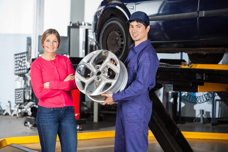 hubcap: Portrait of confident mechanic holding hubcap with female customer at garage