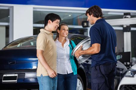 hubcap: Happy male technician showing metallic hubcap to couple at garage
