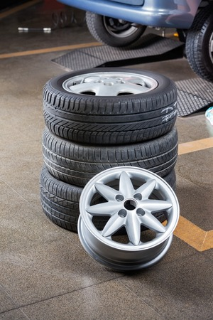 tire: Stack of tires and hubcap at auto repair shop