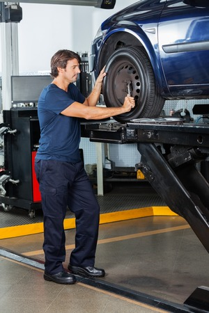 lifted: Male mechanic fixing lifted car tire at auto repair shop