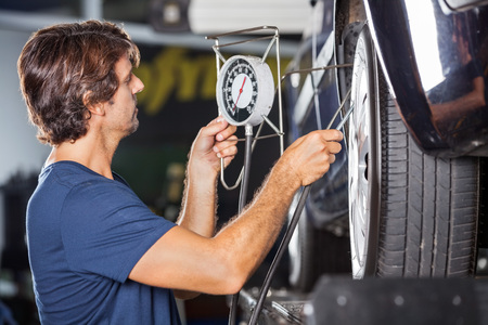 inflating: Side view of mechanic checking pressure while inflating car tire at garage Stock Photo