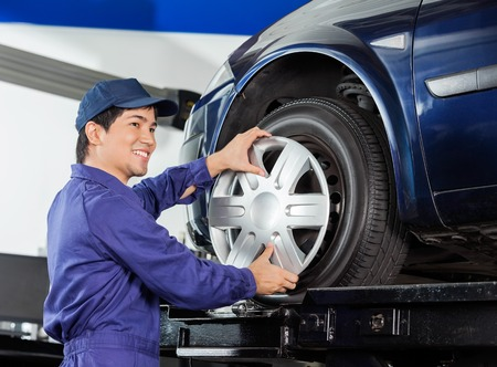 Smiling young mechanic fixing alloy to car tire at garage