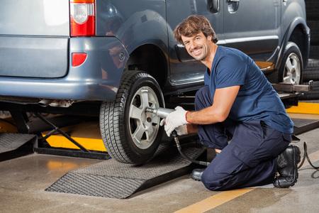 kneeling: Side view of portrait confident male mechanic fixing car tire at auto repair shop