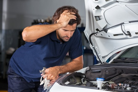 job engine: Confused male mechanic examining car engine at auto repair shop