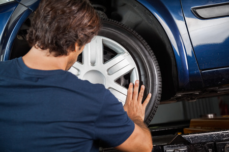 hubcap: Rear view of male mechanic fixing hubcap to car tire at garage