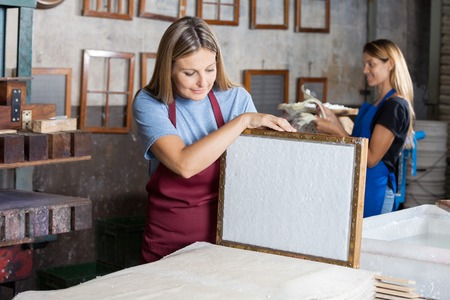 Mid adult female worker looking at dried paper on mold in factory