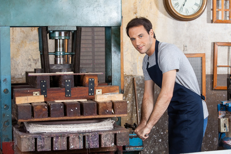 craft paper: Portrait of confident man using paper press machine in factory Stock Photo