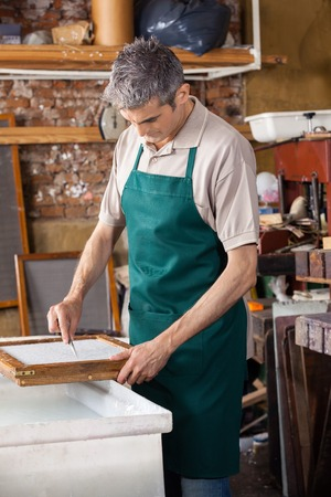 deckle: Mature male worker cleaning paper with tweezers in factory Stock Photo