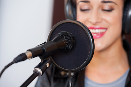 condenser: Closeup of mike and condenser with young woman singing in recording studio