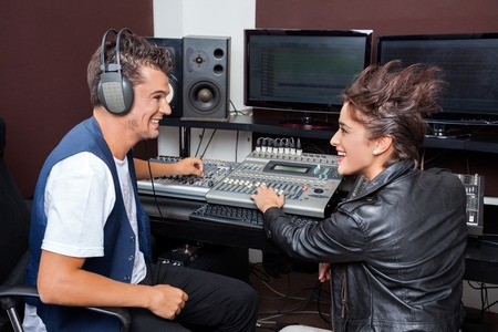 music production: Happy young man and female professionals mixing audio in recording studio