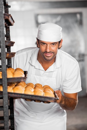 panino: Portrait of confident male baker removing baking tray from rack in bakery