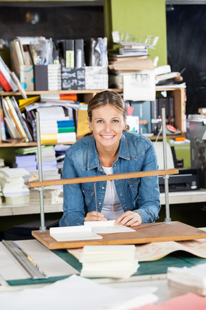 binding: Portrait of happy mid adult woman binding papers at workbench in factory Stock Photo
