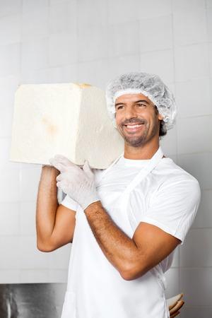 shoulder carrying: Happy mid adult male baker carrying big bread loaf on shoulder in bakery