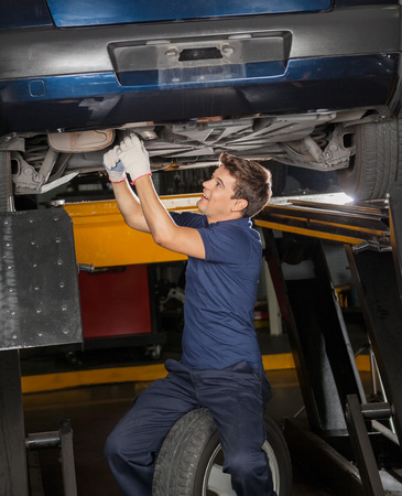 underneath: Young male mechanic repairing underneath lifted car at auto repair shop Stock Photo