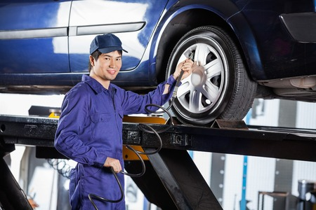 tire repair shop: Portrait of smiling male mechanic filling air into car tire at garage