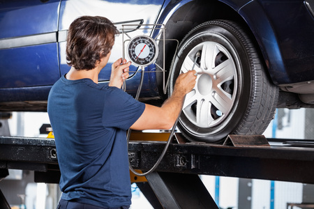 inflating: Rear view of male mechanic looking at gauge while inflating car tire at garage Stock Photo