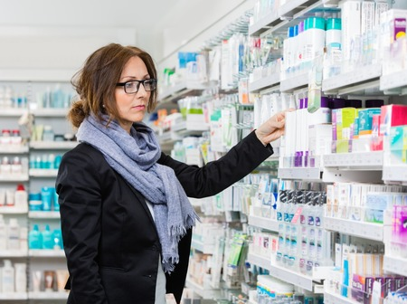 mid adult   female: Mid adult female purchaser choosing product in pharmacy